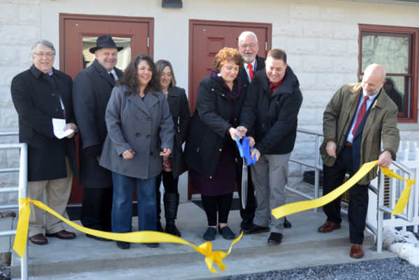 Pictured during the ribbon cutting ceremony at the Merit House are, from left, Commissioners Paul Conklin and Jeff Snyder; Laurie Welch and Bobie Joe Brungard, Clinton County Housing Coalition board members; Maria Garlick, CCHC executive director, and Jeff Rich, Clinton County Housing Authority director, hold the sizzors; Commissioner Pete Smeltz (in back); and Rick Vilello, deputy secretary for community affairs and development at the PA Department of Community and Economic Development.