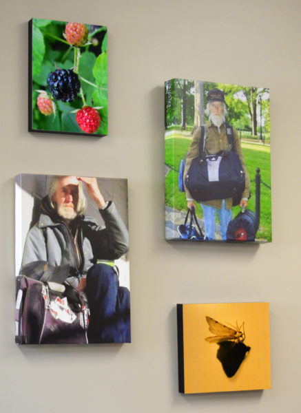Photos of nature and Glenn Merritt, a homeless man who lived in the area for about eight years and for whom the Merit House is named, decorate a wall inside the men's shelter.
