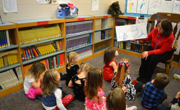 Students in the pre-kindergarten program at Robb Elementary school are seen listening to a story read to them by librarian Kim Bailey.