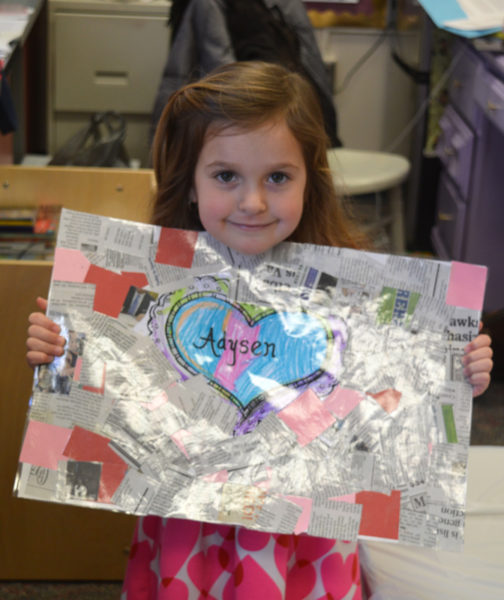 Adysen, 4, proudly displays the placemat she made.