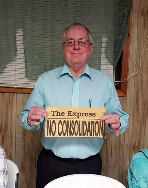 "Dr. Conly holds a newspaper headline from 1995 that reads ""No Consolidation""."